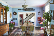 This funky dining room has blue walls and lots of antique and found items.