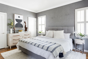 A gray bedroom with a white area rug, modern art, and an upholstered bed.