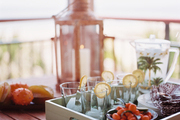 A tray of beverages and a lantern on an outdoor table
