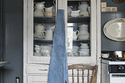 A vintage cupboard housing a full dinner service of ironstone china for 16