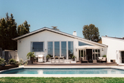 A rectangular pool outside a midcentury home
