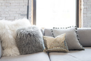 Variety of throw pillows on gray couch.
