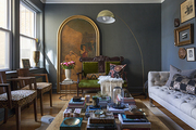 A living room painted with Farrow & Ball's Down Pipe and furnished with leopard chairs, an oversize floor lamp, and a cocktail table filled with objets