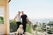 Kevin Howells, Hadi Halawani, and Cooper, a white Lab, on the balcony of their Los Angeles home