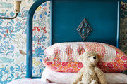 A floral wallcovering behind a navy blue twin bed