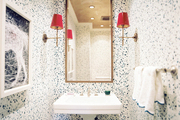 Splatter wallpaper and red-lacquered lampshades in a powder room