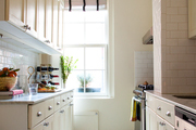 Checkered floors and yellow cabinets in the window-lit kitchen.