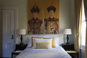 Yellow window drapes, throw pillows, and embroidered wall tapestries accent a guest bedroom.