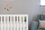 White crib next to a tufted rocking chair in a nursery.
