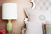 A green lamp on a white bedside table against grass-cloth wallpaper
