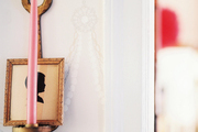 A candle sconce and a framed silhouette hung against patterned wallpaper