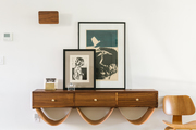 A custom-made shelf with artwork on it and an Eames chair next to it.