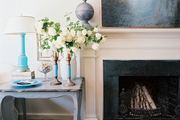 A blue end table beside a fireplace
