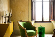 An antique chair next to a contemporary side table and storage unit under frescoed ceilings