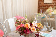 A modern tablescape with pink flowers and pink plates.