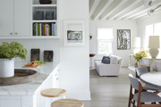 White and wood barstools under marble countertop.