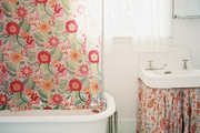 A bathroom with a floral shower curtain, a skirted sink, and a patterned rug
