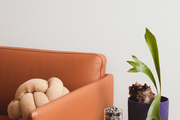A modern living space with an orange leather couch.