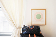 Framed artwork hung above stacked leather luggage