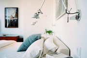 Swing-arm sconces above an upholstered bed outfitted with white and blue bedding