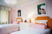Large-scale photographs above orange upholstered headboards and pink bolster pillows