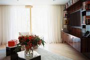 A wooden built-in media center balanced by white curtains
