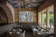 A brick arch near a ceiling mural, artwork, and tufted leather banquettes at the Distrit Miami