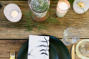 A rustic tablescape with black plates and gold cutlery.