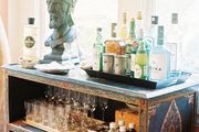 Trays of bar essentials and glassware surrounding a bust