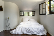 Over sized white bedding in rustic bedroom,