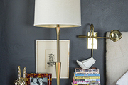 A nightstand with vintage items against a wall painted with chalkboard paint