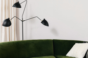 This living room has a green velvet couch and mid-century floor lamp.