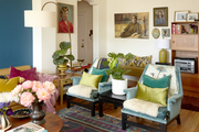 Two blue armchairs in an eclectic and colorful living room.