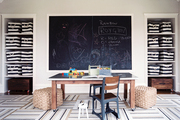 A geometric rug and a large chalkboard in a play space