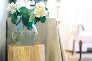 A tree-trunk end table topped with a vase of flowers