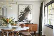Dining room table with abstract art hanging.