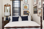Traditional white bedroom with blue and brown accents, and a gallery wall.