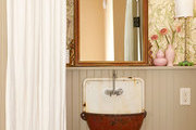 A rustic, vintage sink is paired with an antique mirror and marbled wallpaper in a New Orleans guest bath