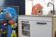 An upstairs playroom is outfitted with a toy kitchen from IKEA.