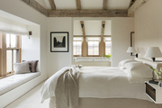 White bedding and window bench below natural wood beams.