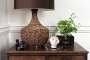 A traditional brown cabinet with a brown cork lamp.