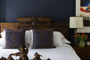 A carved headboard against a navy wall