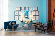 Gallery walls above a seating area with CB2's Avec Peacock sofa at Jessica Alba's Honest Company office