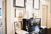 A gallery wall of art above a black cabinet