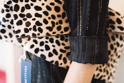 A mannequin holding a fold-over animal-print clutch