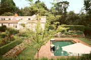 A rectangular pool and gardens surrounded by boxwoods