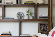 A bed sitting next to a bookshelf holding plates, books, and ceramic pieces.