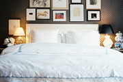 A grouping of art above an upholstered headboard paired with white scalloped bedding