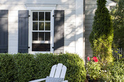 A white Adirondack chair  in a front yard lined with shrubs