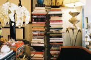 Stacks of books and a glass-topped table in a living space with a zebra-hide rug